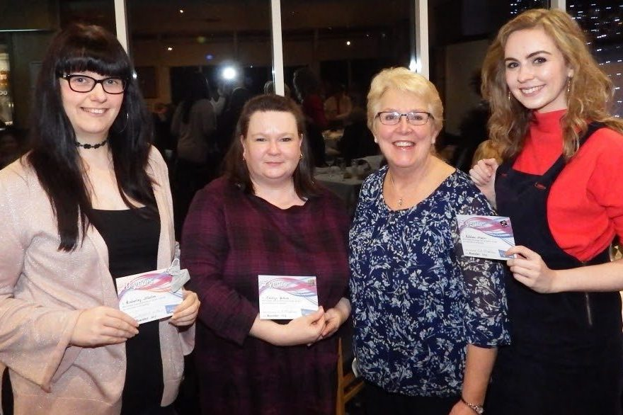 Adult members stand with service awards
