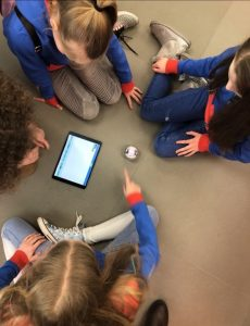 Guides sitting on the floor around an ipad