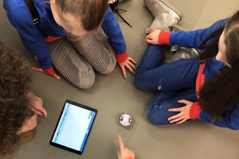 Guides sit on the floor around a tablet