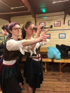Two leaders dressed as pirates with a telescope