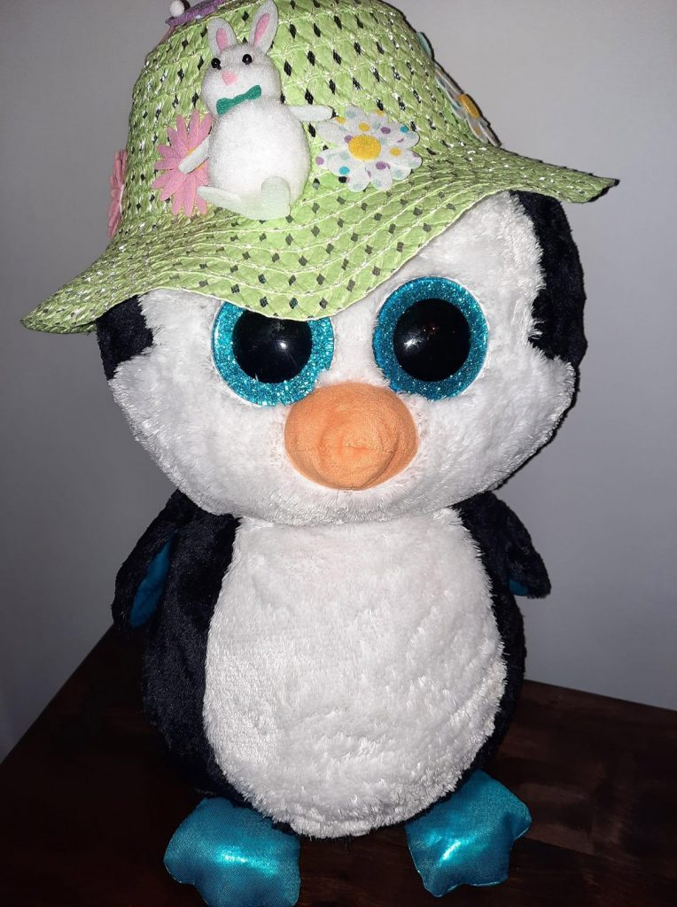 Pale green bonnet decorated with flowers and a small rabbit, modelled on a toy penguin