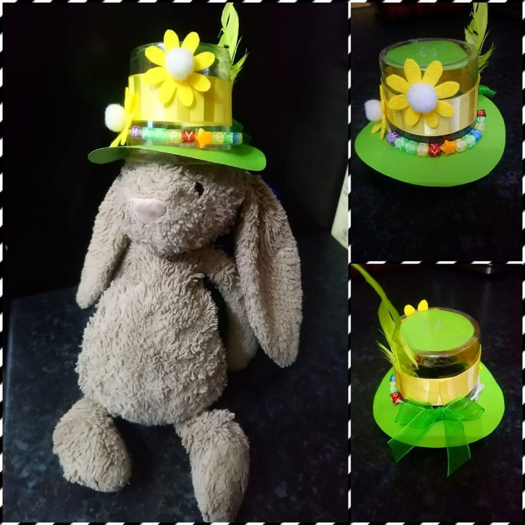 Green bonnet decorated with paper flowers and ribbon, modelled on a toy rabbit