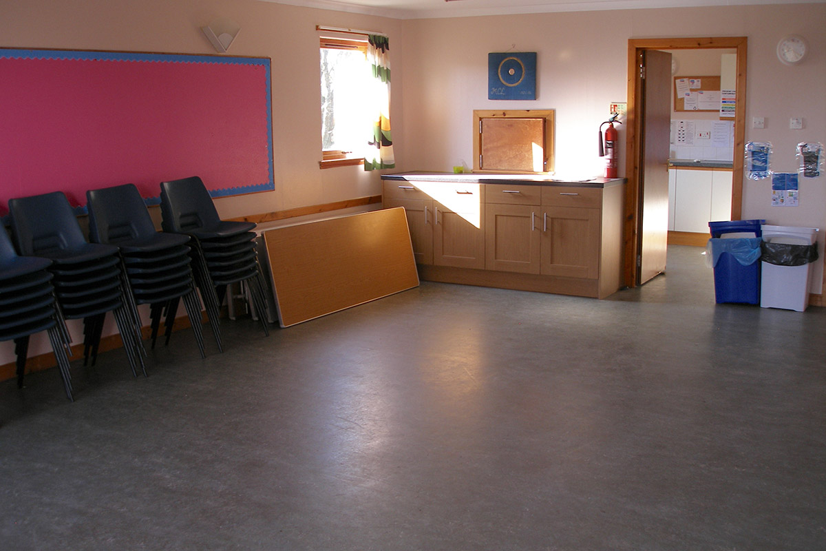 Activity room with chairs to side and kitchen door to back