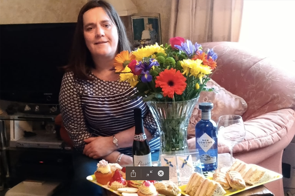 Woman surrounded by gifts of flowers, cake, and gin