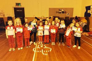 Rainbows holding their certificates behind their Trefoil candle