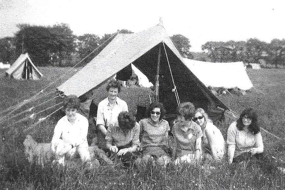 A group of women sit outside of a canvas ridge tent