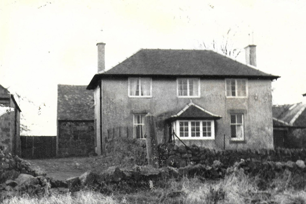 Black and white image of a farm house behind a small wall with a barn in the bakcground