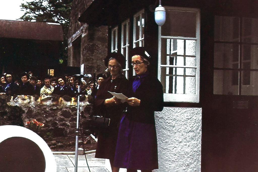 Two women stand behind a microphone outside of a farm house