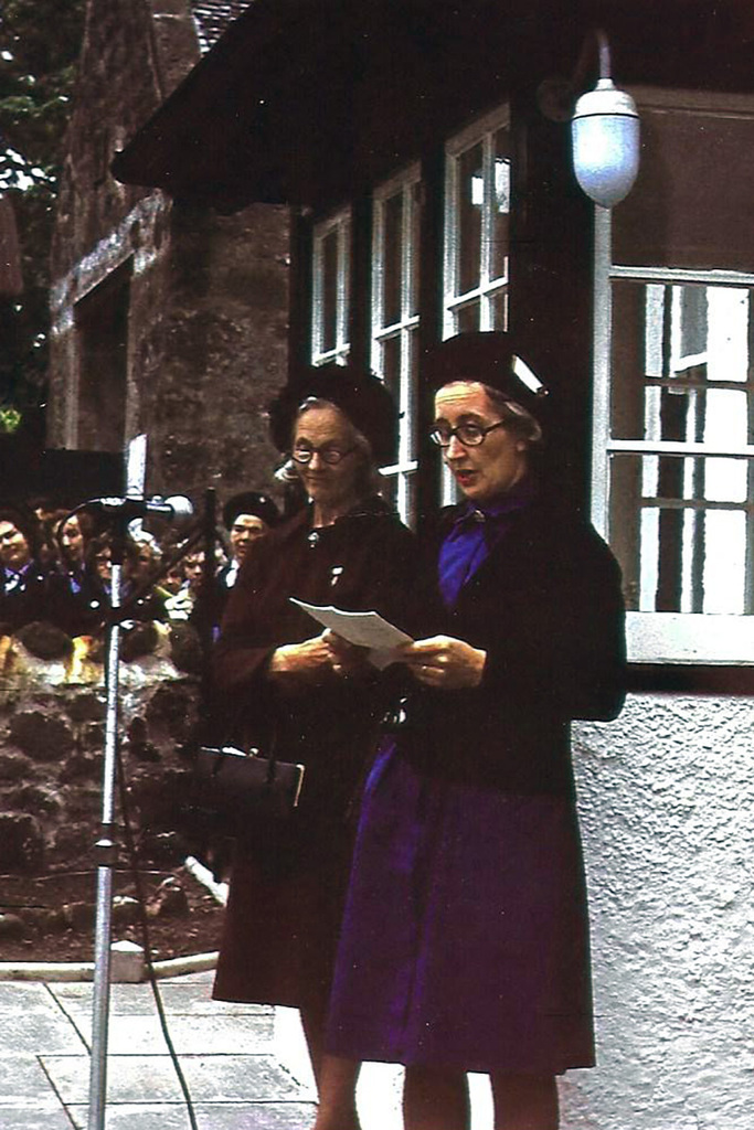 Two women stand by a microphone outside of a white farm house