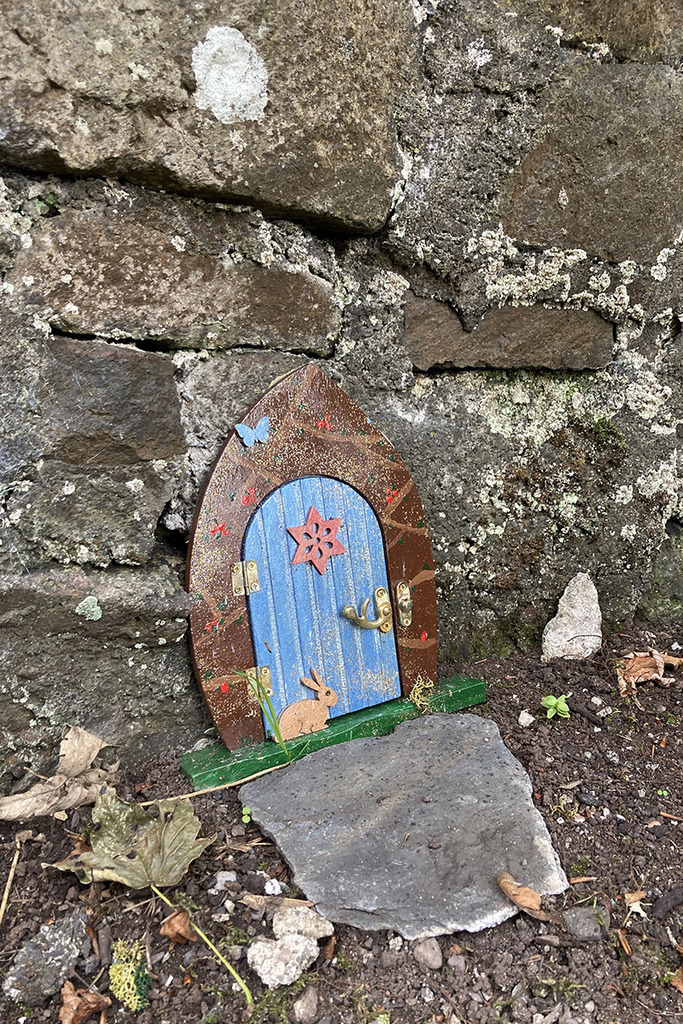 """A small """"fairy door"""" against a rock wall. the door is blue with a brown doorframe, and has a star and rabbit on it."""