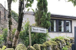"""A sign that says """"South Newton"""", in the background is Lomas, (a large bungalow)"""
