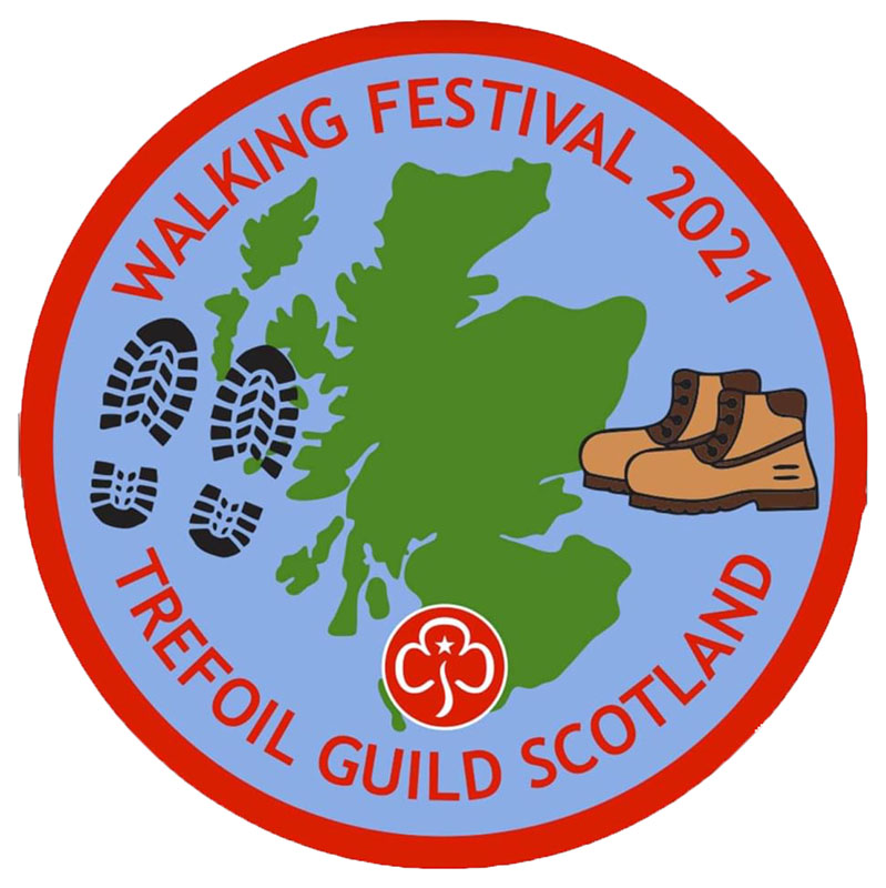 """A badge with a map of Scotland in green in the centre, footprints to the left, and walking boots to the right. In a curve in red writing at the top of the badge is """"WALKING FESTIVAL 2021"""" and at the bottom """"TREFOIL GUILD SCOTLAND"""" with the Trefoil Guild logo above the bottom text. The border of the badge is red."""
