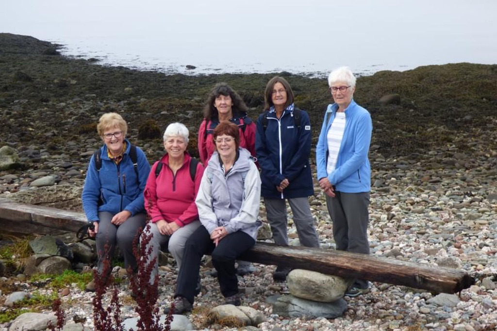 A group of six women at a pebblestone beach. Three are sitting on a long piece of driftwood made into a bench, and three others stand behind them.