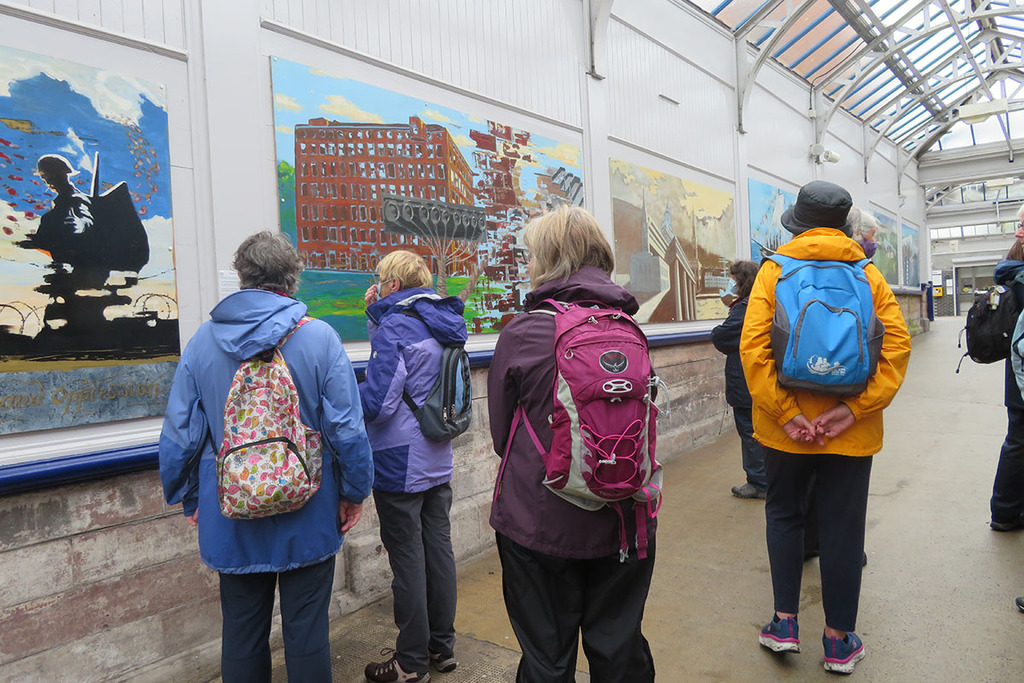 Four women standing looking at artwork in what looks like a train station. The artwork is of a silhouetted soldier (likely a memorial piece), and a large brown building (unsure of what this is).