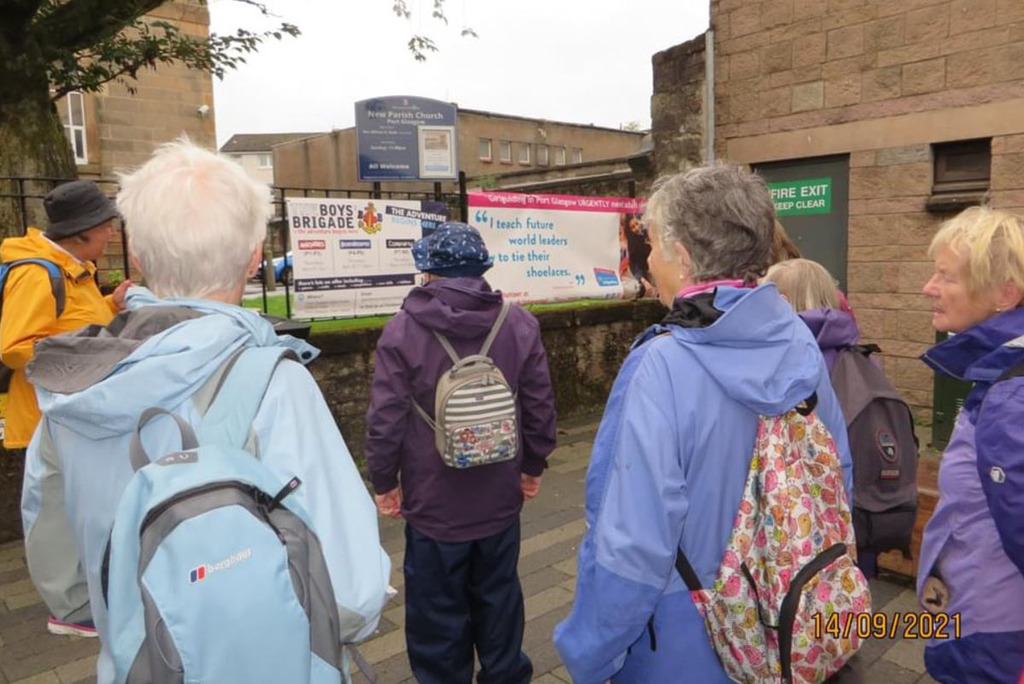 Six women all look towards a Girlguiding recruitment sign. The women are all wearing jackets and backpacks of different colours. They are looking at the recruitment banner that is on railings.