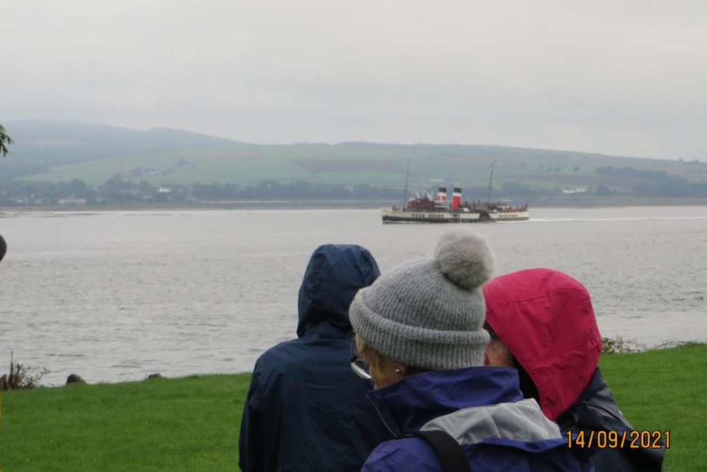Three women stand in the foreground, and in the middleground is the Waverly: a paddle steamer. The sky is grey.